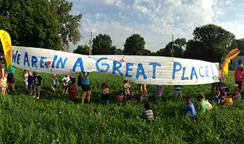 """Indianapolis kids holding a sign that says """"We are in a great place!"""""""